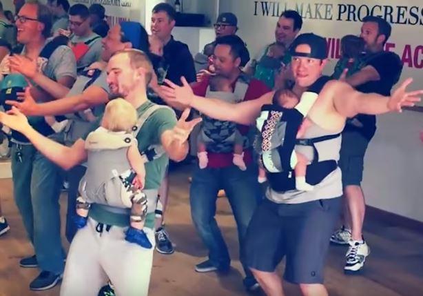 Frischgebackene Väter tanzen mit ihren Babys