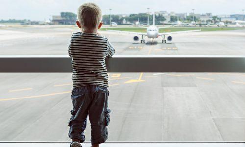 Weibliche Fluggäste helfen überforderten Mutter am Flughafen